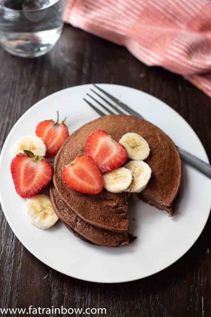 Chocolate protein pancakes served with strawberry slices and banana with napkin and a glass of water in the back