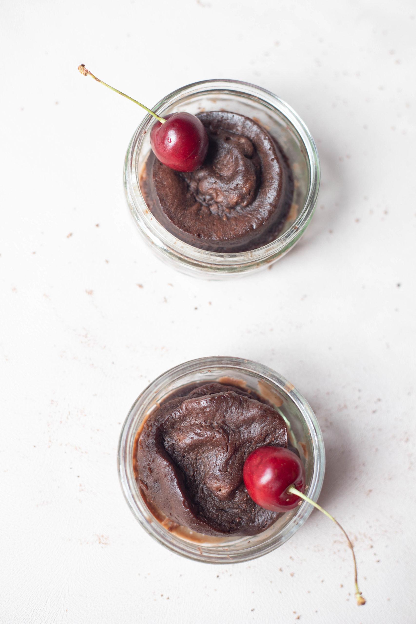 2 chocolate mug cakes with cherries on top