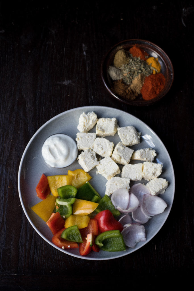 paneer, bell peppers, yogurt on a plate along with spice powders