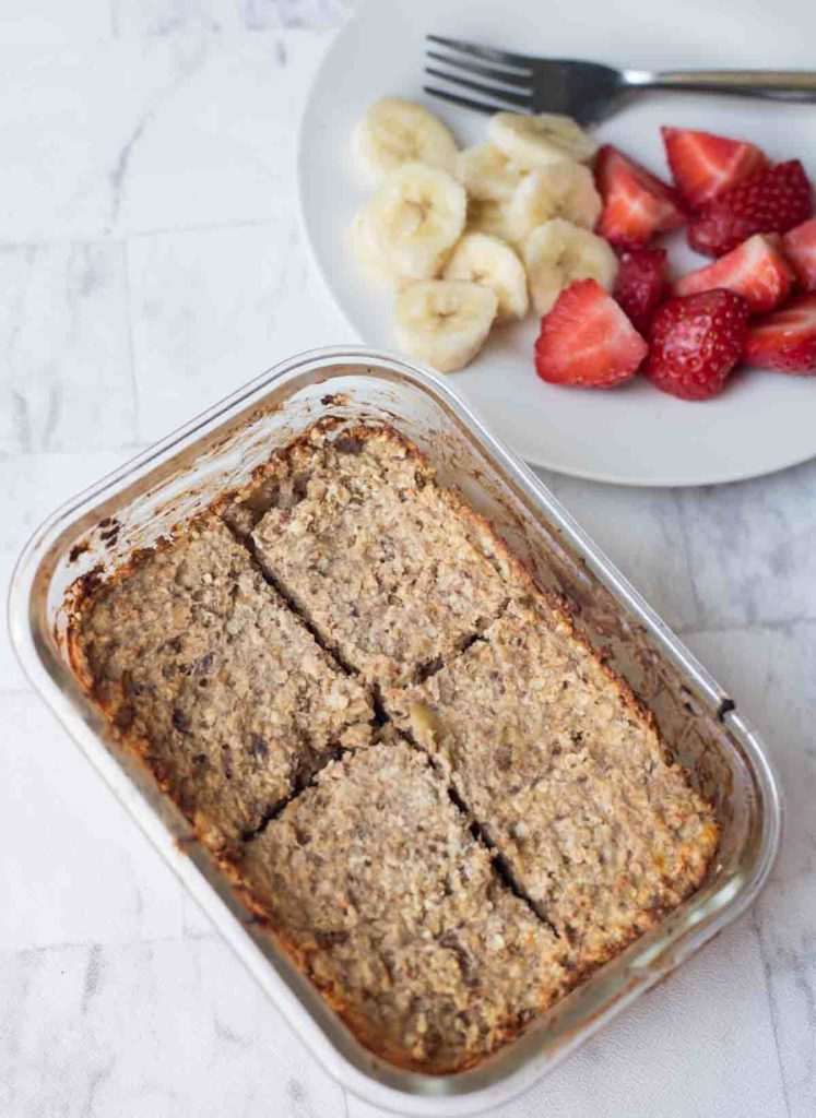 Baked oatmeal in a pyrex dish with fruit on the side