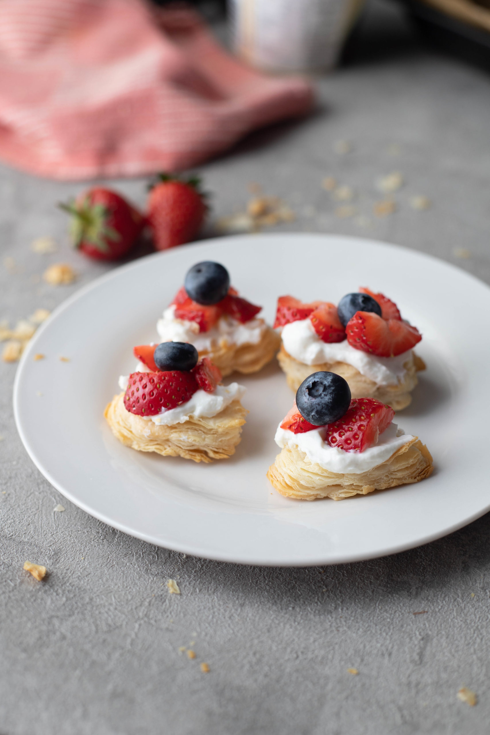 strawberry Puff pastry bites served with cream and berries
