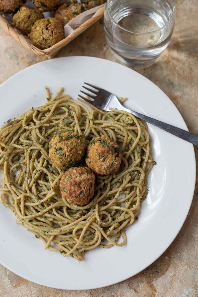 vegan spinach lentil meatballs served on pesto pasta with a glass of water