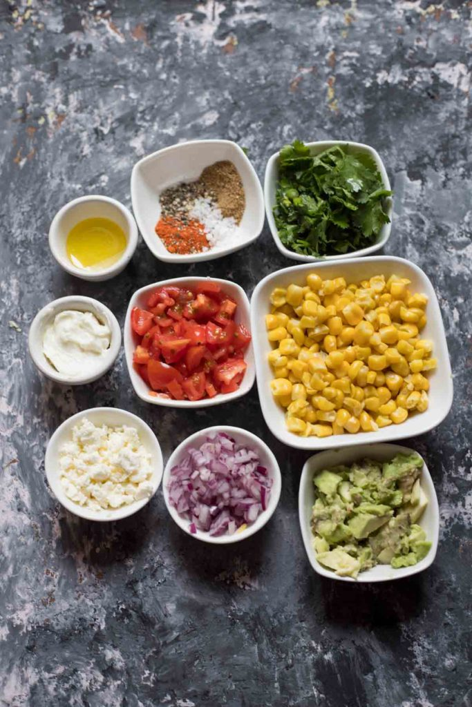 Ingredients for mexican street corn salad, sweet corn,avocados,red onions,feta cheese tomatoes olive oil, spices coriander,quark
