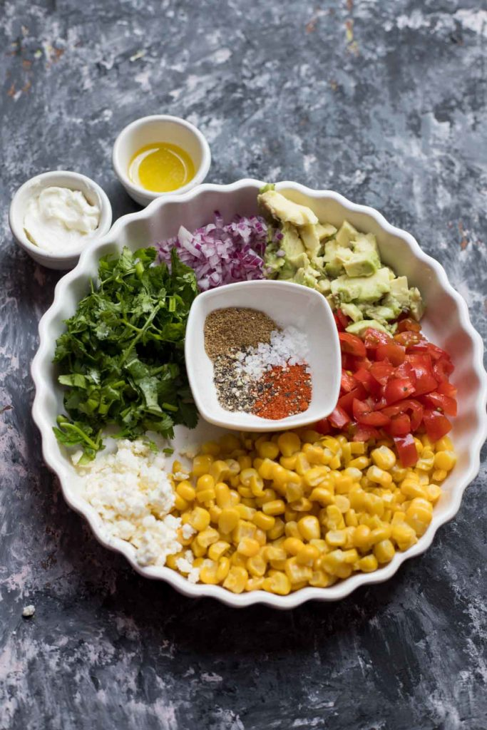 Mexican street corn salad served in a white plate with silver spoon