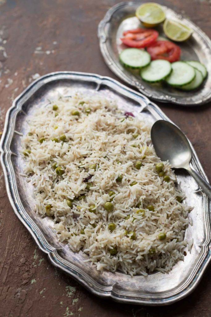 Instant Pot Green peas pulao served on a silver plate and onion, tomato salad