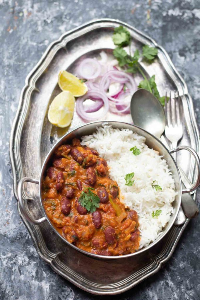 Rajma Masala curry served with basmati rice in a steel kadai placed on a large plate with onion rings, lemon wedges and cutlery