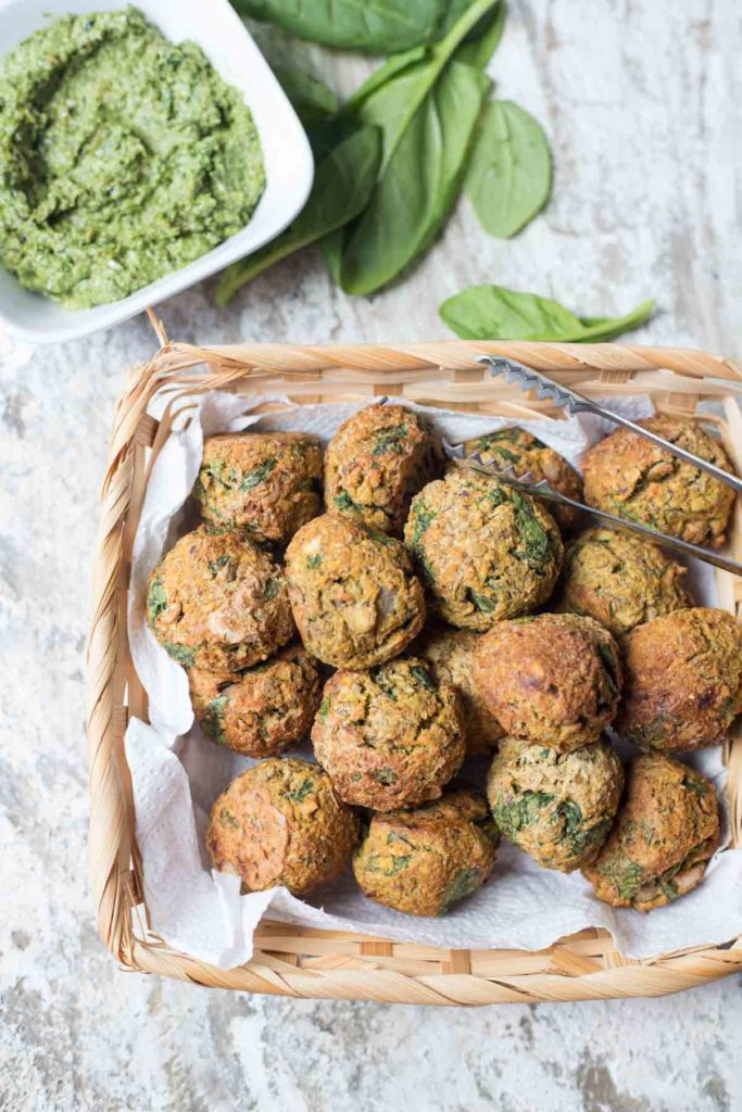 vegan spinach lentil meatballs with basil pesto and spinach leaves in the background
