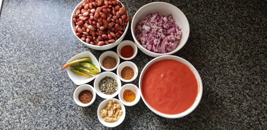 Ingredients to make instant pot Rajma Masala - beans,chopped onions. tomato puree, green chilli, spice powders like cumin, coriander,red chilli, turmeric