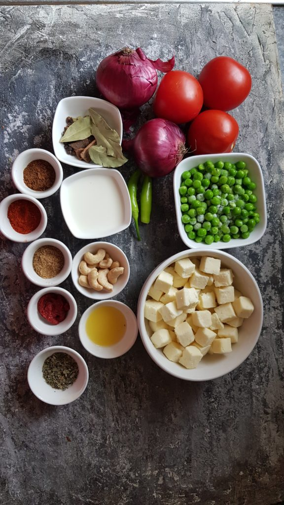 Ingredients to make instant pot matar paneer, onions, tomatoes, cashews, milk, chilli, whole spices, butter, spice powders.