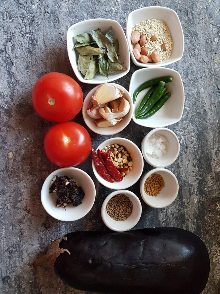 Ingredients for making vankaya pachadi, tomatoes, eggplant, garlic cloves, green chillis, curry leaves,urad dal,channa dal, mustard seeds, dried red chillis,tamarind