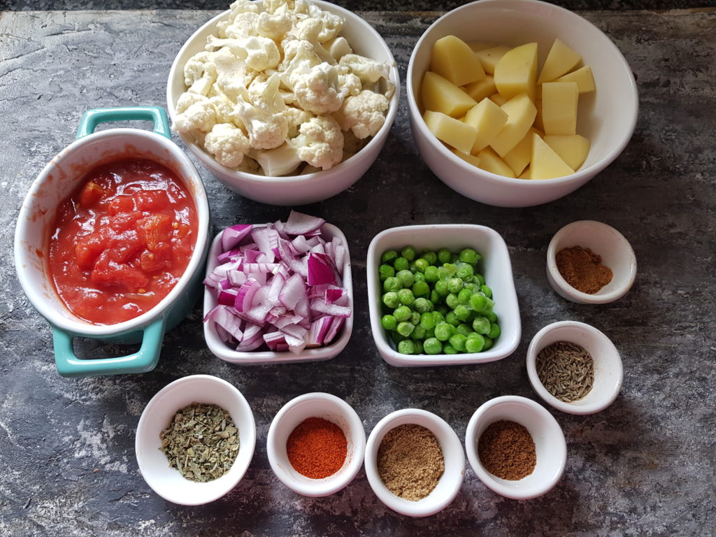 ingredients for making aloo gobi, tomatoesm potatoes, cauliflower,onions,peas, spice powders,cumin seeds