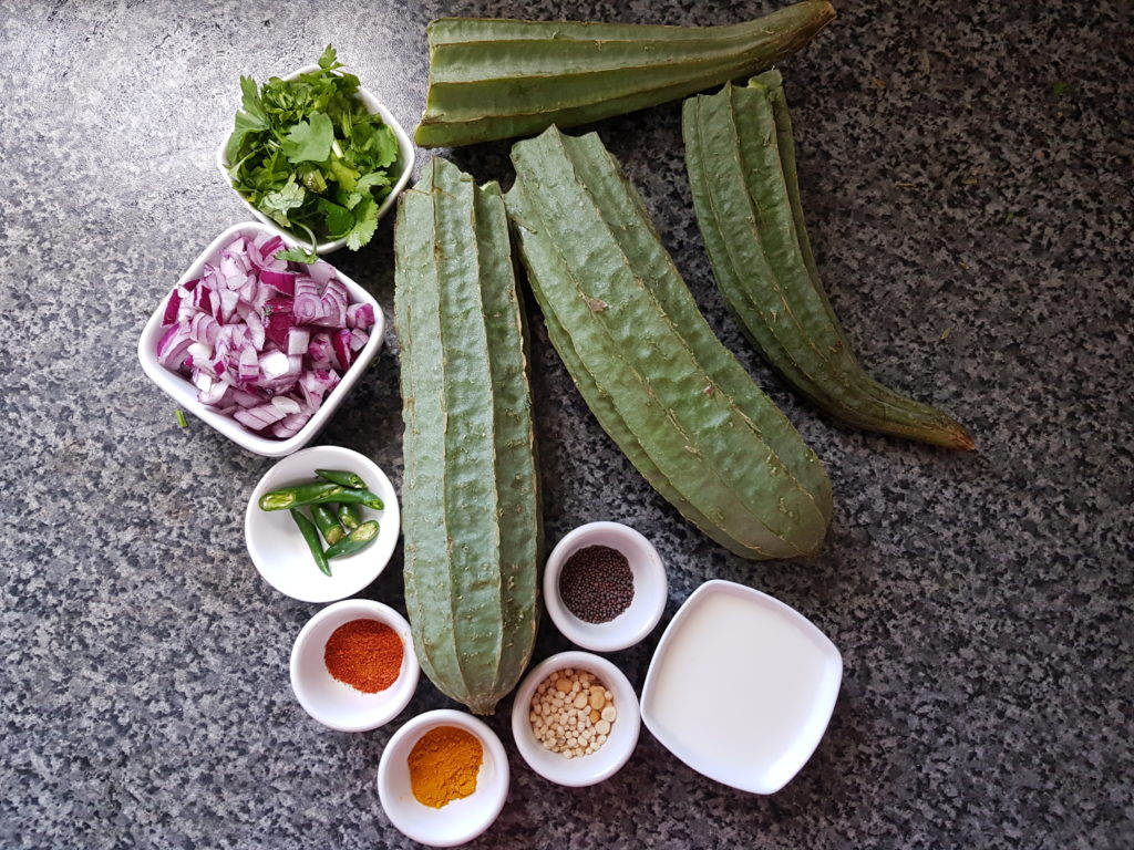 ingredients for ridge gourd curry , ridge gourd, chopped onions,green chilli, spice powders, mustard seeds, milk