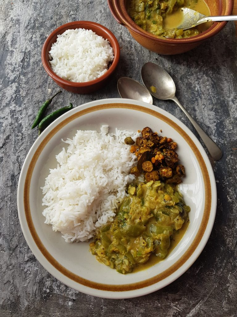 a plate of rice served with ridge gourd curry