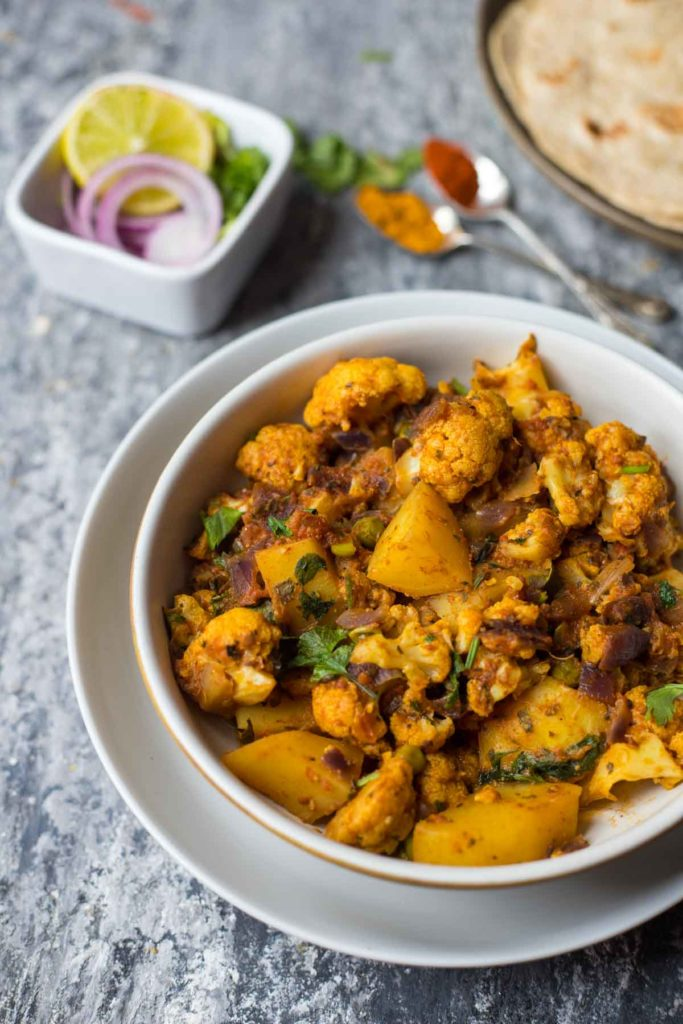 bowl of aloo gobi with rotis and onion,lemon