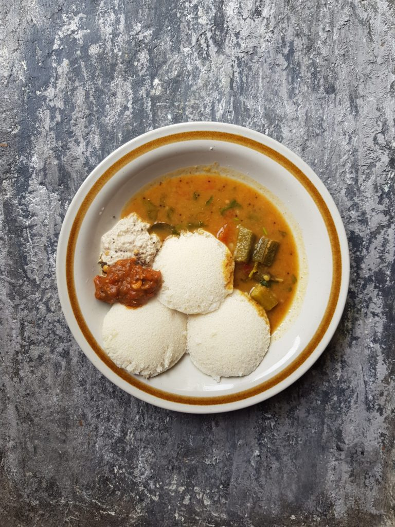 idlis served with sambar and chutneys