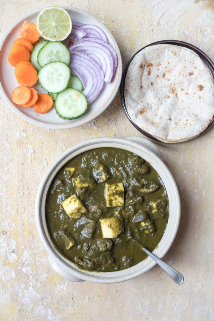 mushroom palak paneer served in a white bowl, rotis, salad