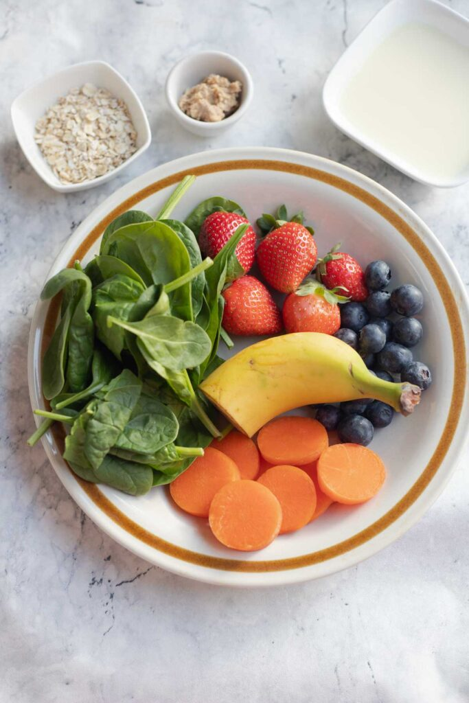 a plate loaded with berries, banana, carrots,spinach and a bowl of oats , milk and peanut butter