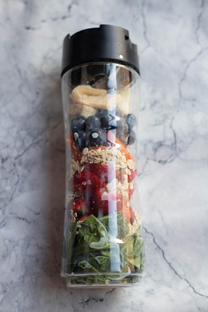 berries, oats,banana,spinach,carrots in a blending jar