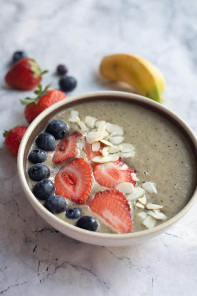 banana berry smoothie bowl topped with berries and almond flakes
