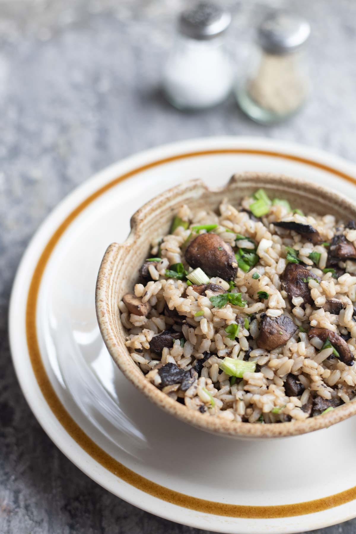 a bowl of mushroom fried rice with chopsticks