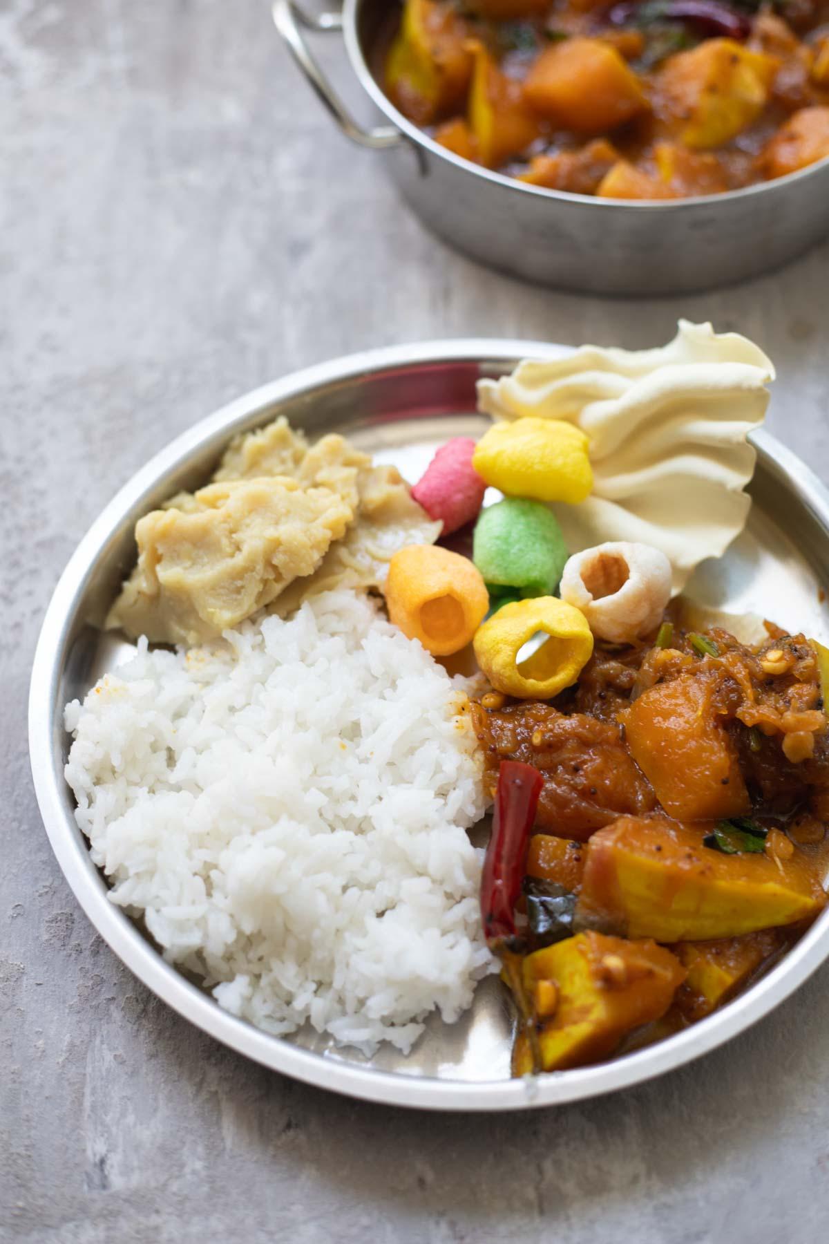 an ndian thali plate with rice, gummadikaya pulusu ,dal, papads