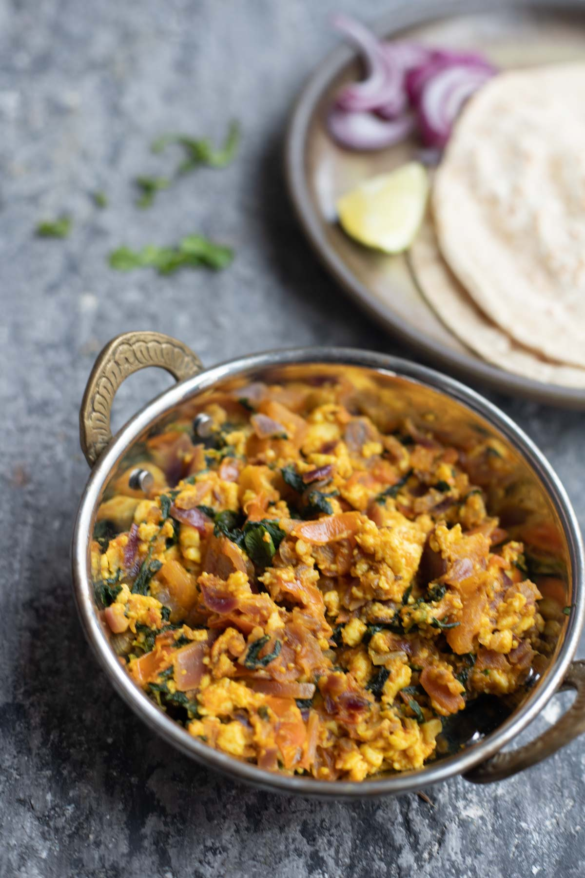methi paneer bhurji in a steel kadai with a plate of rotis , onion and lemon salad in the background