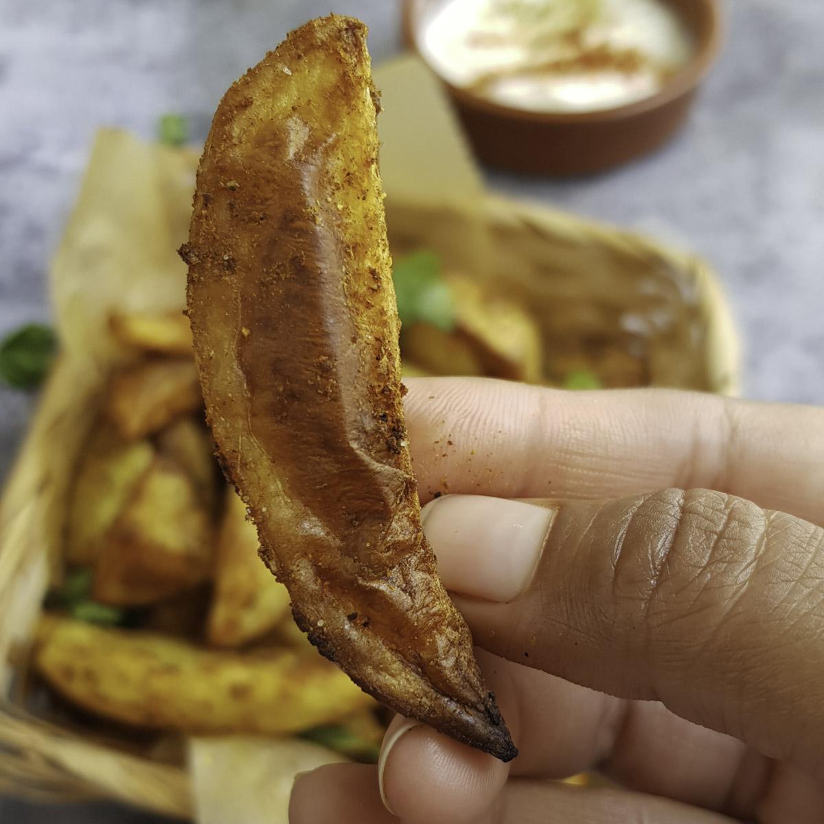 a hand holding crispy crusted potato wedge