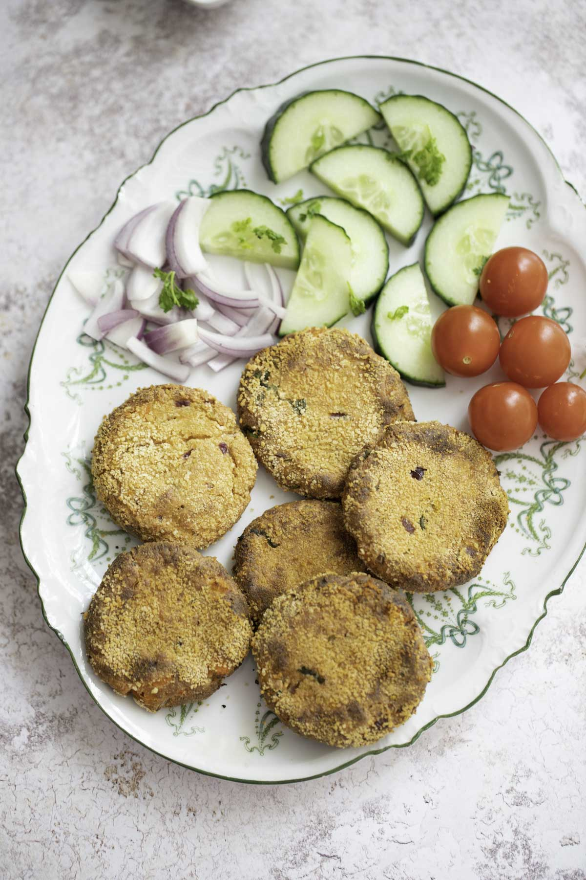 baked paneer cutlet served with salad on a plate