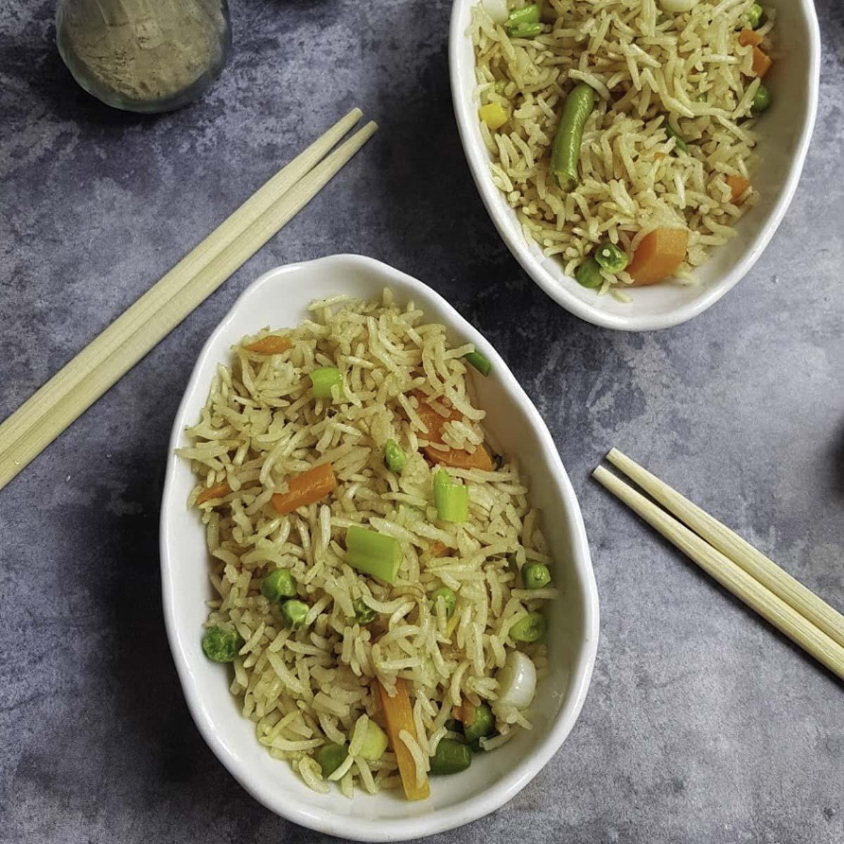 a bowl of baked fried rice , 2 chopsticks