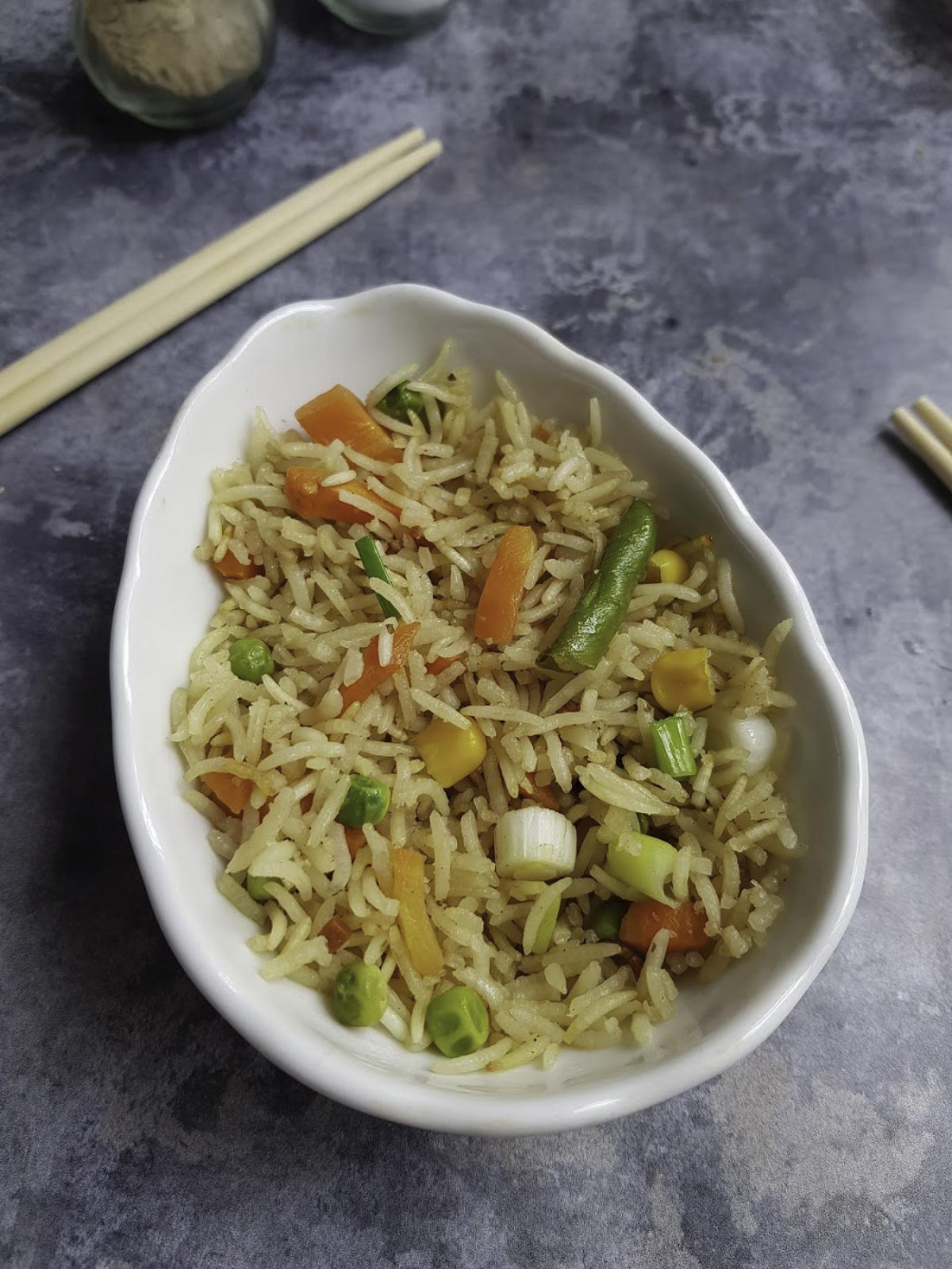 a small bowl of fried rice served with chopsticks in the background