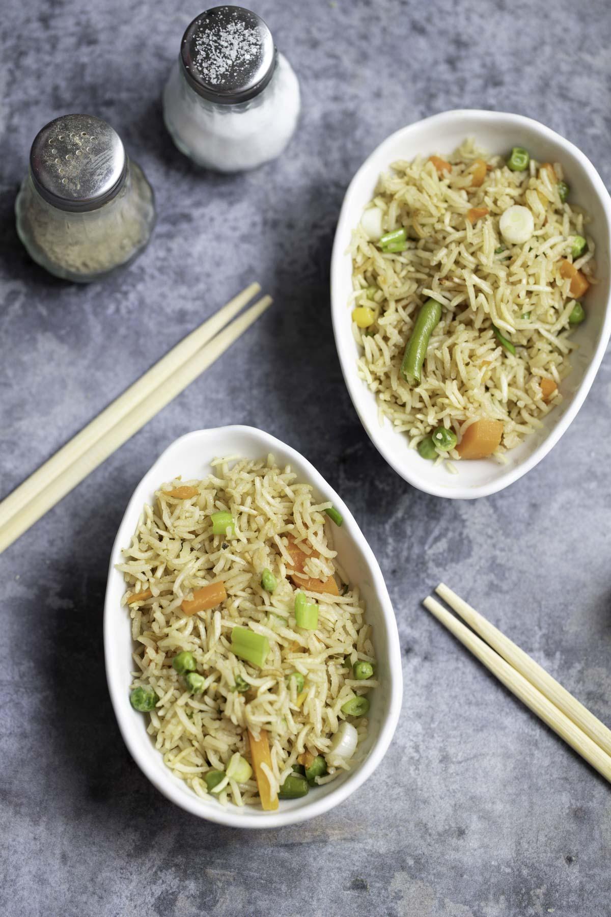 2 bowls of baked fried rice , 2 chopsticks, salt and pepper