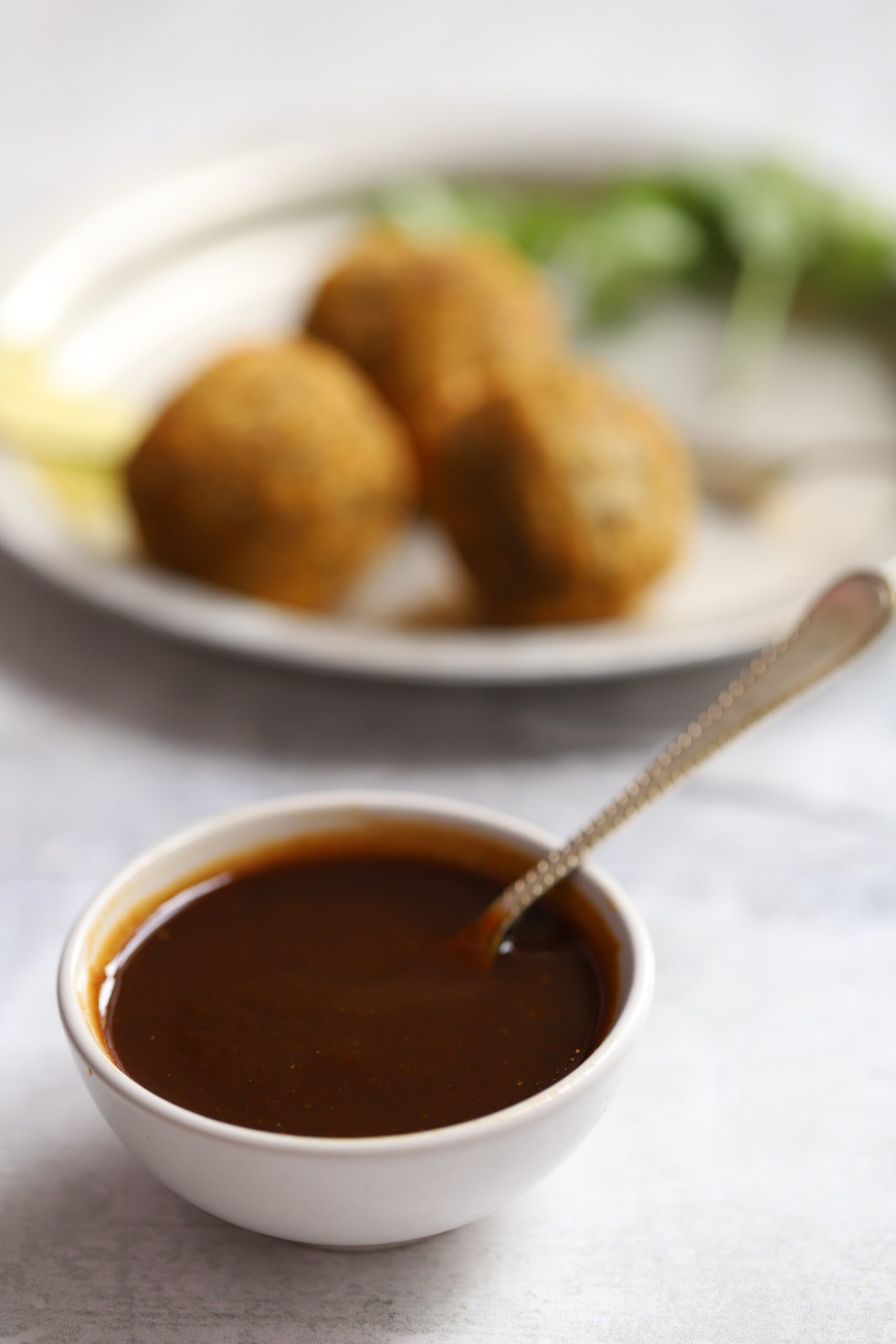 a small bowl of tamarind sauce with serving spoon