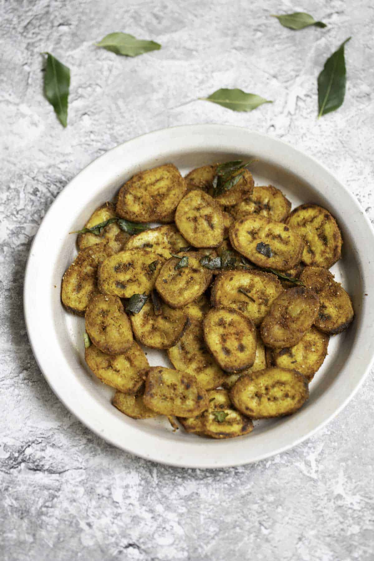 a plate of raw banana fry with curry leaves in the background for decor