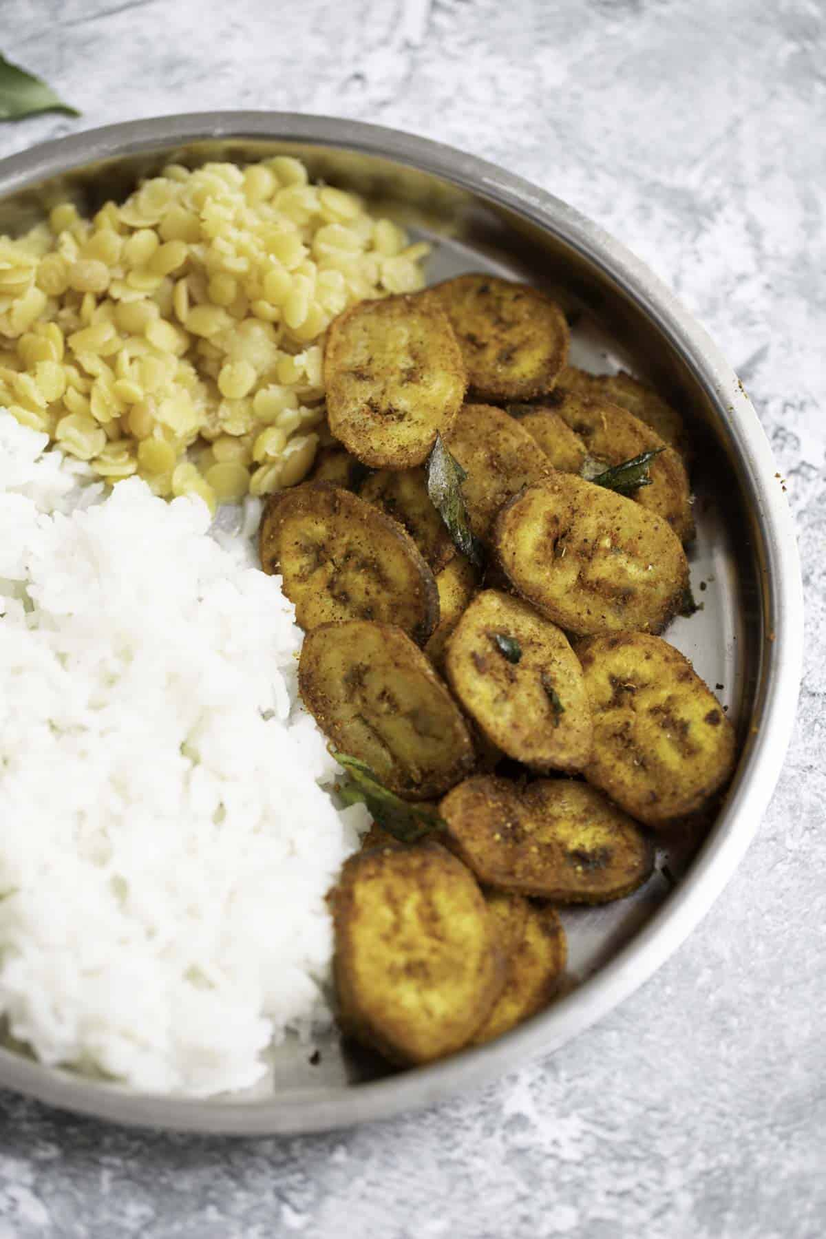 a plate of cooked white rice, dal, raw banana fry
