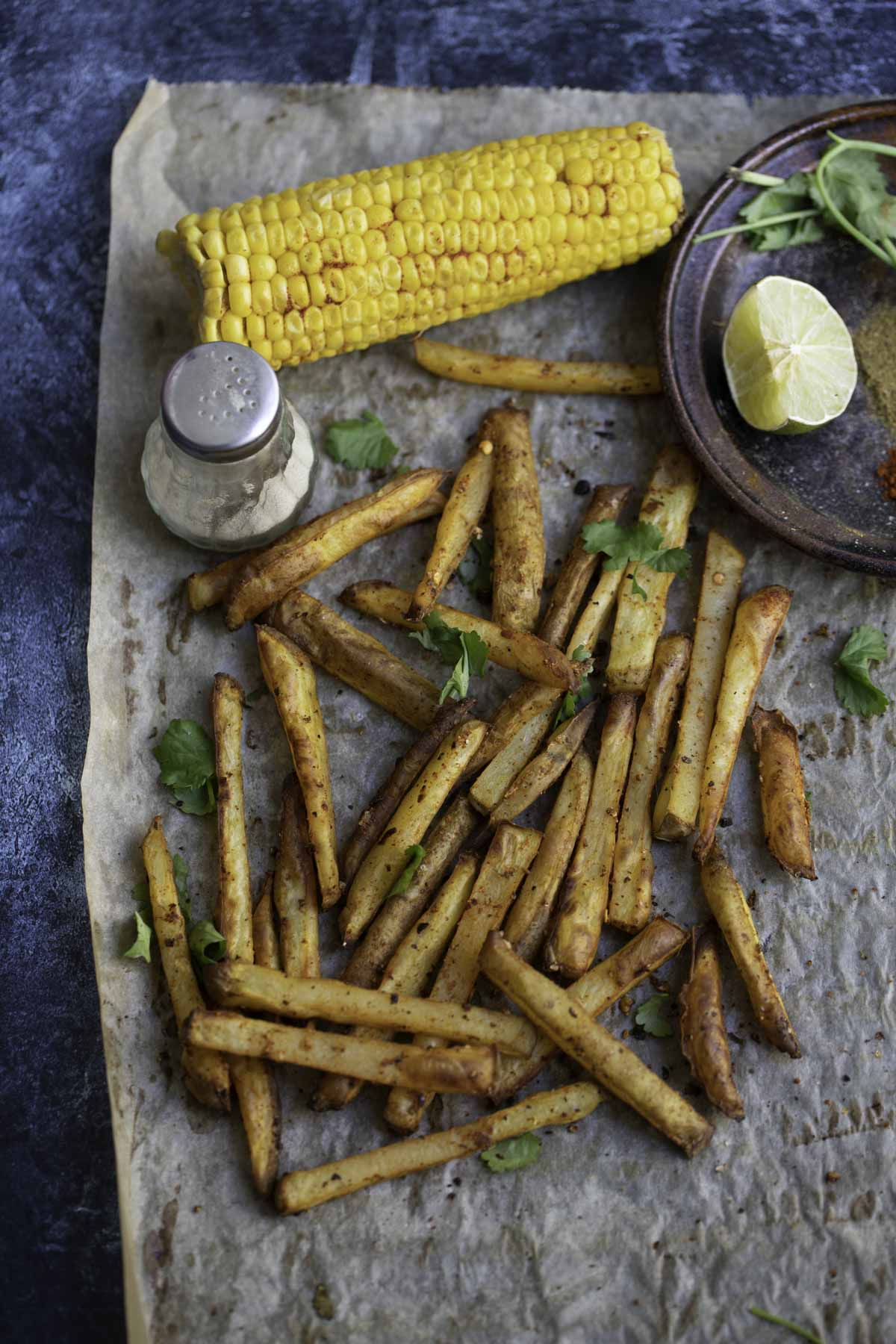 baked masala fries on a baking paper. pepper, corn on the cob and a lemon wedge in the background