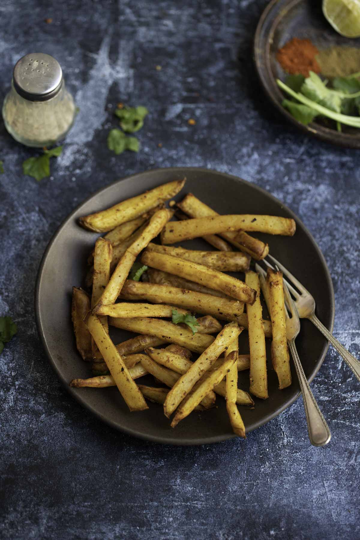 a plate of masala fries with salt and pepper to back of it