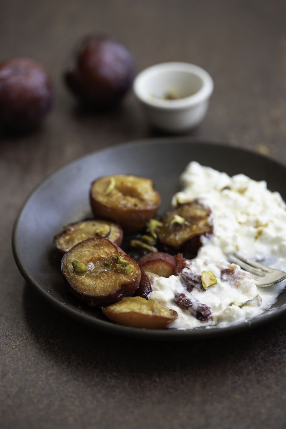 roasted plums served with cottage cheese and garnished with pistachios