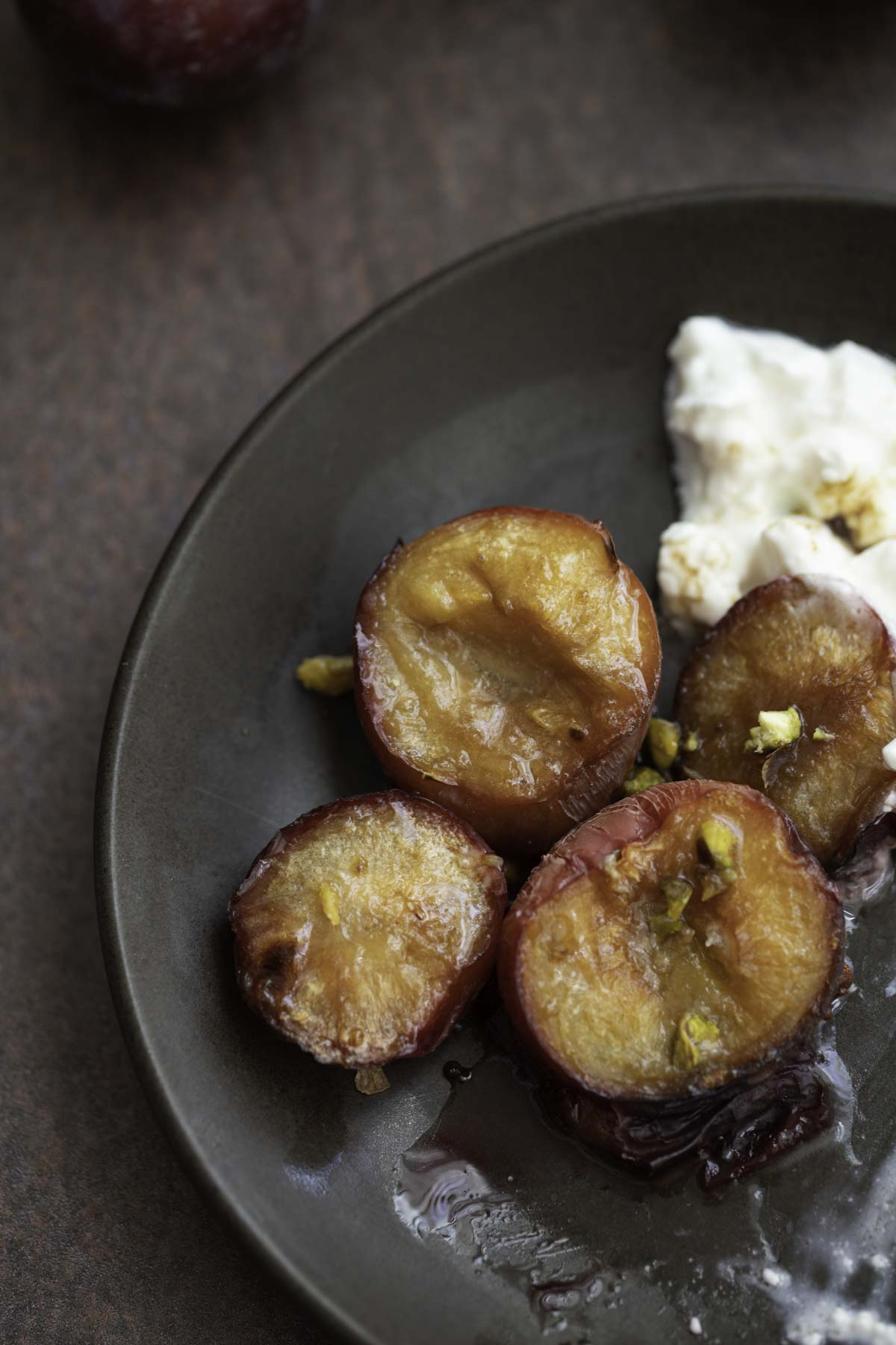 roasted plums with a drizzle of honey and garnished with pistachios