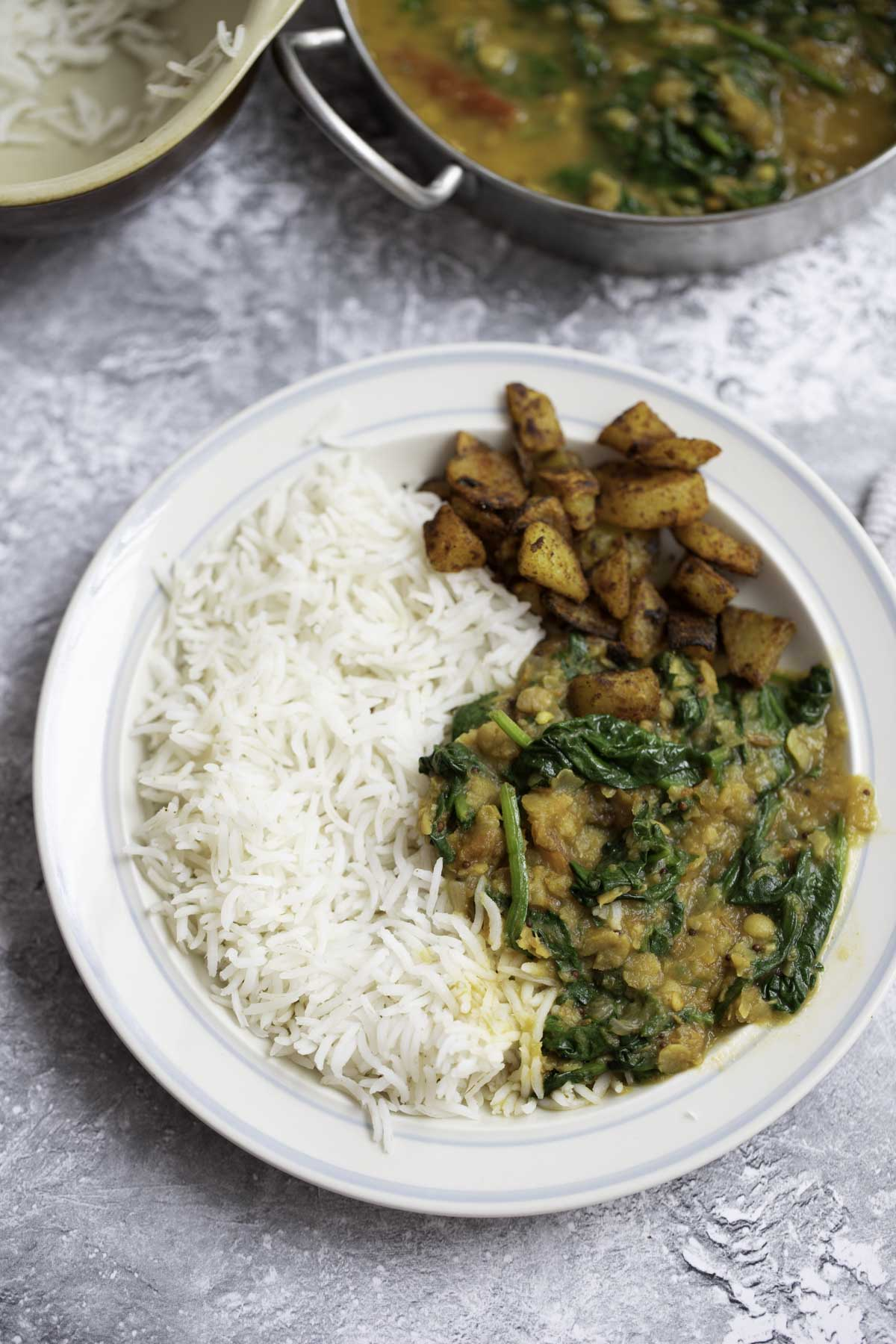 a plate of rice, spinach dal and roasted potatoes