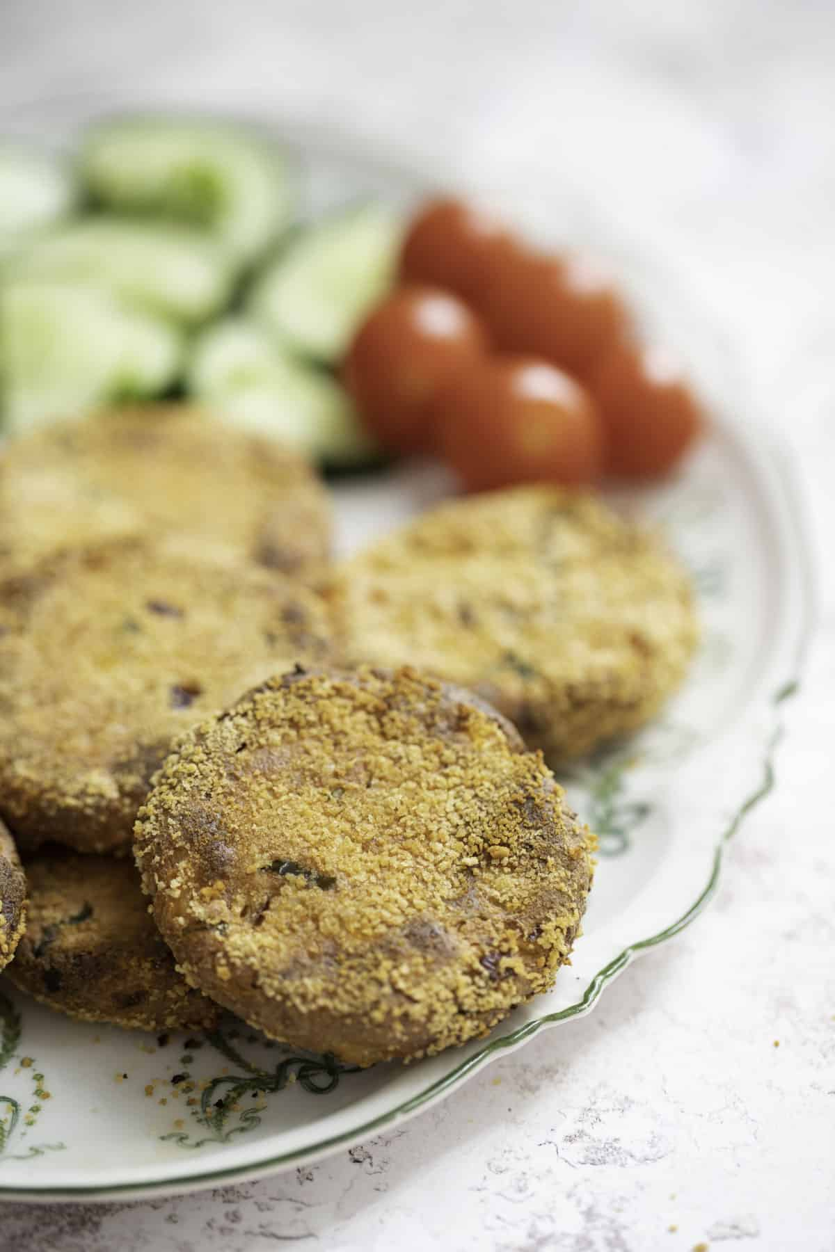 crispy baked paneer cutlets served with cucumber and tomato salad